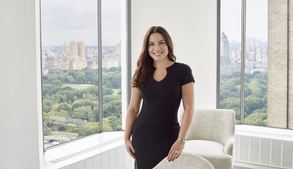 Gina Mallick, commercial insurance and risk manager for J.T. Magen, stands in a client's office overlooking Central Park.