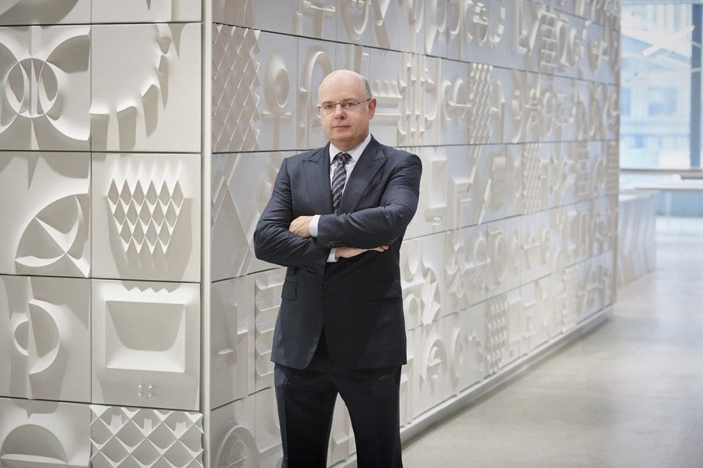 Maurice Regan, CEO and founder of J.T. Magen, is posed in a dark suit against a white wall textured with geometric designs.