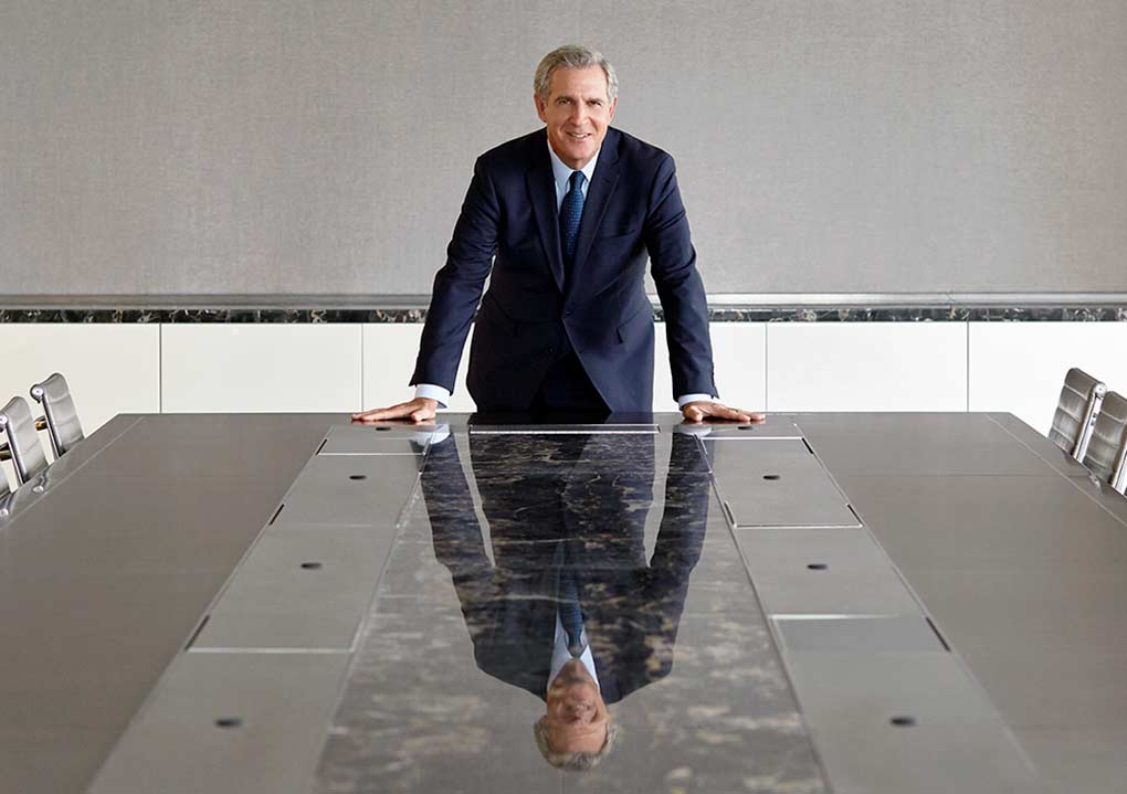 Robert Scheinman, principal at J.T. Magen, commands attention standing at the head of a long, sleek conference room table.